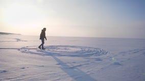 Enfoque amplio hacia fuera tirado del hombre alegre en perfil que camina rightwards en sol en campo nevoso almacen de video