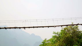 Enfoque, cacerola, mujer turística que cruza puente colgante de bambú peligroso almacen de video