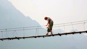 Enfoque, cacerola, mujer turística que cruza puente colgante de bambú peligroso metrajes