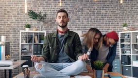 Enfoque en el time lapse del individuo que medita que se sienta en el escritorio de oficina en la posición de loto almacen de metraje de vídeo