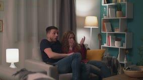 Enfoque en el tiro de pares jovenes en el sofá tarde en la noche que mira una película de terror asustadiza almacen de metraje de vídeo