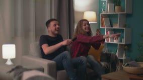Enfoque en risa tirada del hombre y de la mujer mientras que ve la TV en sala de estar por la tarde almacen de video