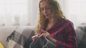 Enfoque fuera de la mujer joven que se sienta en el sofá y que hace punto en hogar almacen de metraje de vídeo