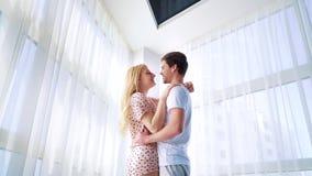 Enfoque fuera del hombre joven y de la mujer en los pijamas que abrazan cerca de ventana curtained almacen de metraje de vídeo
