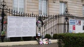 Enfoque hacia fuera de los juguetes y de las flores a la fachada de la bandera rusa de la media asta de la embajada del consulado almacen de video