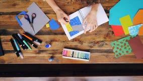 Enfoque-hacia fuera del dibujo de papel de fabricación moreno creativo del collage con los creyones que se sientan en el escritor almacen de video
