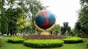Enfoque hacia fuera - manos gigantes que sostienen el globo - Hanoi Vietnam almacen de video