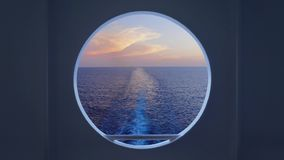 Enfoque hacia fuera a través de porta del ` s del barco de cruceros sobre estela posterior metrajes