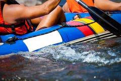 Enfoque a una cierta parte de la persona joven están transportando en balsa en el río Fotos de archivo