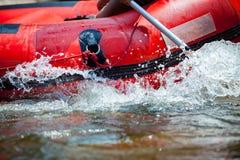 Enfoque a una cierta parte de la persona joven están transportando en balsa en el río Imágenes de archivo libres de regalías