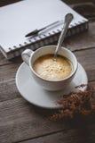 Enfríese y relájese con café y el cuaderno calientes en de madera viejo adentro Foto de archivo libre de regalías