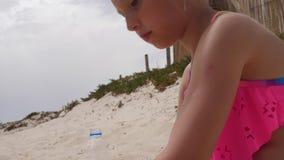 Enfrente a menina feliz que joga e que faz o bolo de areia e forme-a na praia do verão video estoque