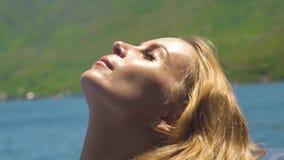 Enfrente o banho de sol bonito da mulher no dia ensolarado na paisagem do mar Feche acima da jovem mulher do retrato com cabelo d filme