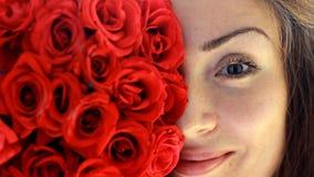 Enfrente o close-up de uma jovem mulher bonita com rosas vermelhas anunciar Anúncio video estoque