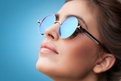 Enfrente o retrato da mulher bonita nova em óculos de sol redondos Fotografia de Stock Royalty Free
