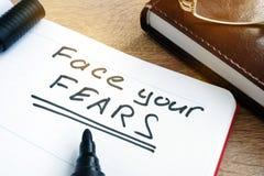 Enfrente seus medos escritos em uma nota fotografia de stock
