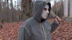 Eng karakter in eng Halloween-masker en machete in het park stock video