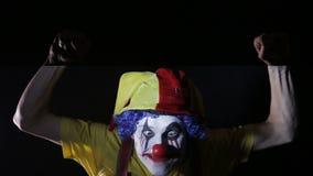 Eng schot van een griezelige gekke clown die angstaanjagende gezichten in donkere ruimte maken onder stroboscoop Portret stock video