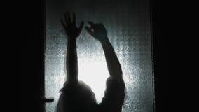 Eng silhouet achter de deur stock video