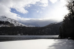 Engadin谷在有雪的瑞士Sils玛丽亚村庄在阿尔卑斯山和冻湖 图库摄影