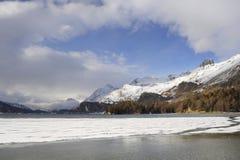 Engadin谷在有雪的瑞士Sils玛丽亚村庄在阿尔卑斯山和冻湖 免版税图库摄影