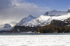 Engadin valley in Switzerland Sils Maria village with snow on Alp mountains and frozen lake Stock Photos