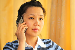 Engage with technology. A young women occupied on a phone Royalty Free Stock Image