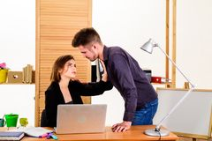 Engaged in affair. Relations at workplace. Handsome man and sexy woman having romantic relations at work. Love relations. Between female and male coworkers royalty free stock photo