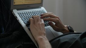 Engaged bright man searching the web. Young businessman lying down using laptop stock footage