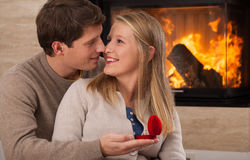 Engaged couple at home. A freshly engaged couple sitting at home by a fireplace Stock Photo