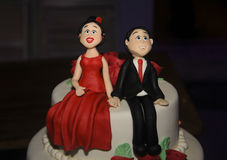 Engaged Couple on wedding cake. Multi-tiered wedding cake for the engagement ceremony, made of tasty candy on happy couple figurine Stock Photography