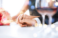 Engaged couple with wine glasses. Love, family, anniversary concept - engaged couple with wine glasses in restaurant Royalty Free Stock Photo