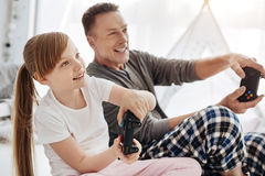 Engaged emotional child and her father using controllers for playing. In another world. Charismatic nice beautiful family enjoying video games while spending Royalty Free Stock Images