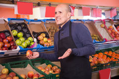 Engaged male vendor selling apples in the grocery store. Engaged mature male vendor selling apples in the grocery store Stock Photo