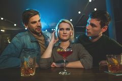 Engaged males molesting frustrated woman. I do not want to tell about it. Portrait of disappointed female talking with two interested guys. Acquaintance with men Royalty Free Stock Image