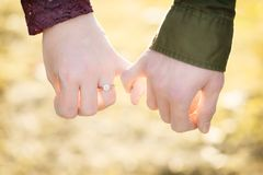 An engaged man and woman hold pinkie fingers showing their love. stock photography