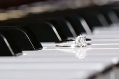 Engaged to Music. Diamond Solitaire Engagement Ring on Piano Keyboard royalty free stock photo