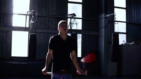 Engagedin som boxas mannen i blått kortslutningsöverhopprep i en boxas idrottshall Cardio genomkörare och boxning Begrepp av ett  arkivfilmer
