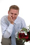 Engagement. A man on his knee with a bouquet of flowers and an engagement ring Royalty Free Stock Images