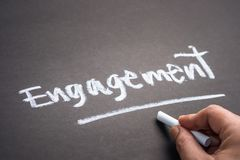 Engagement on Chalkboard. Hand writing the word ENGAGEMENT on chalkboard stock photo