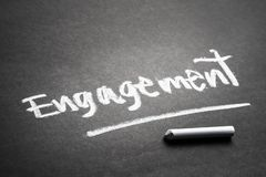 Engagement on Chalkboard. Engagement topic, handwriting by chalk on chalkboard for social media concept stock photography