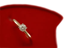 Engagement diamond ring on red. Gold engagement ring with solitaire diamond in red box - closeup, isolated Stock Photo