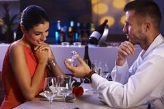 Engagement dinner. Young men proposing to beautiful woman, holding engagement ring, waiting for answer stock photography