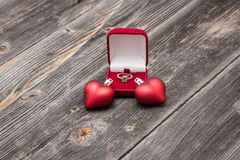 Engagement emerald ring and red hearts Royalty Free Stock Photos