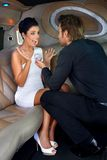 Engagement in limousine. Young men proposing beautiful women in limousine with engagement ring royalty free stock photo