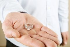 Engagement / marriage / wedding proposal scene. Close up of man handing the expensive gold platinum diamond ring to his bride. Man, fiance, groom to be holds Stock Photos