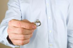 Engagement / marriage / wedding proposal scene. Close up of man handing the expensive gold platinum diamond ring to his bride. Man, fiance, groom to be holds Royalty Free Stock Image