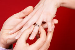 Engagement proposal. Man putting an engagement ring on a woman's hand over red background. Horizontal color image Royalty Free Stock Image