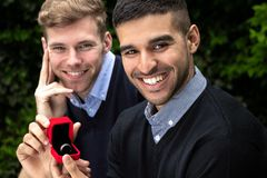 Engagement proposal betwen two gay men as one man proposes with an engagement ring in red box stock photography