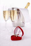 Engagement ring. Wine Glasses with champagne and Engagement Ring, selective focus on nearest Royalty Free Stock Photo